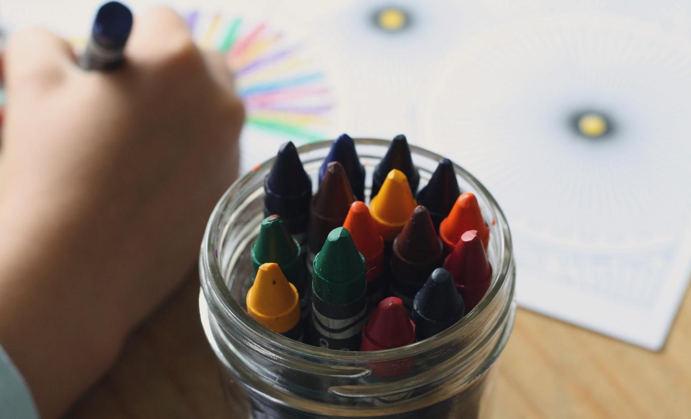 Glas mit Wachsmalstiften, Kind malt ein Bild